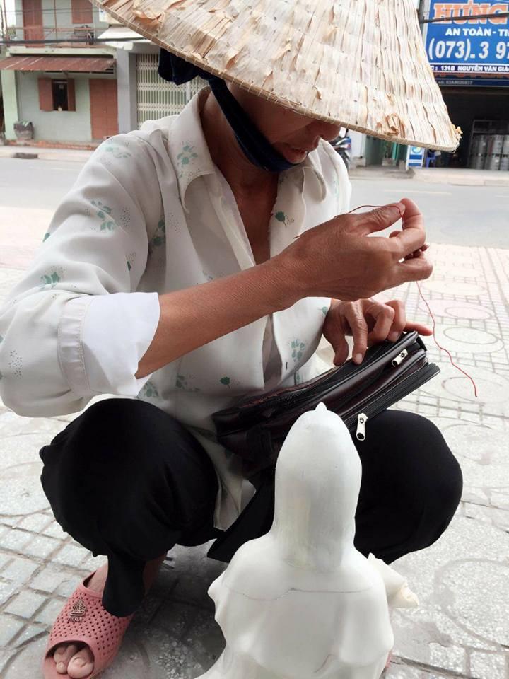 Người đàn bà bán vé số cố gắng sửa lại tượng bà